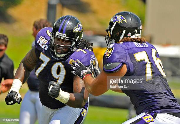 Baltimore Ravens' Oniel Cousins and Jah Reid run through drills during practice in Owings Maryland Monday August 8 2011