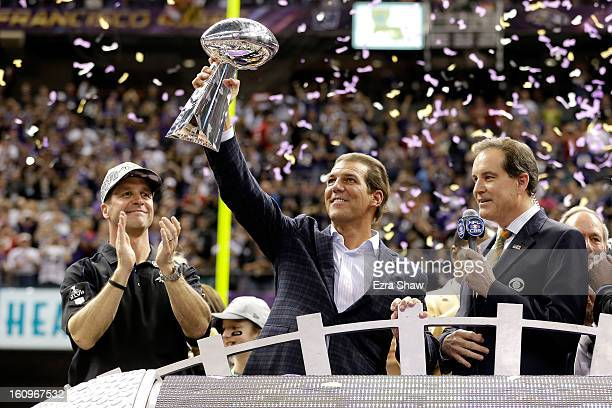 Baltimore Ravens owner Steve Bisciotti and head coach John Harbaugh celebrate with the Vince Lombardi championship trophy on the pdium next to CBS...