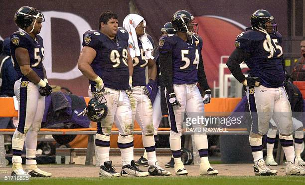 Baltimore Ravens' players Peter Boulware Tony Siragusa Jamie Sharper Shannon Taylorand Sam Adams watch the game from the sideline in the rain during...