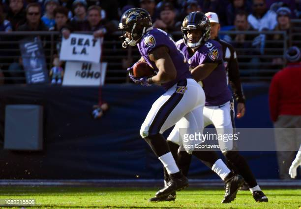 Baltimore Ravens quarterback Lamar Jackson hands the ball off to running back Gus Edwards against the Los Angeles Chargers on January 6 at MT Bank...