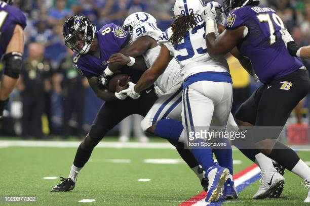 Baltimore Ravens quarterback Lamar Jackson holds onto the football as he is tackled by Indianapolis Colts defensive tackle Hassan Ridgeway in action...