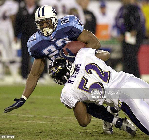Baltimore Ravens' Ray Lewis tackles Tennessee Titans' running back Eddie George during first half action 12 November 2001 of their NFL game at...