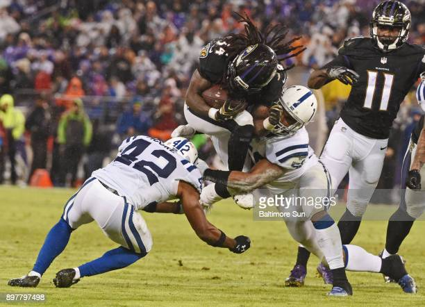 Baltimore Ravens running back Alex Collins middle jumps through the Indianapolis Colts' Kenney Moore II and Anthony Walker for a first down in the...