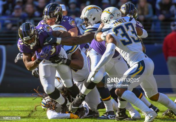 Baltimore Ravens running back Gus Edwards is brought down by Los Angeles Chargers strong safety Jahleel Addae on January 6 at MT Bank Stadium in...