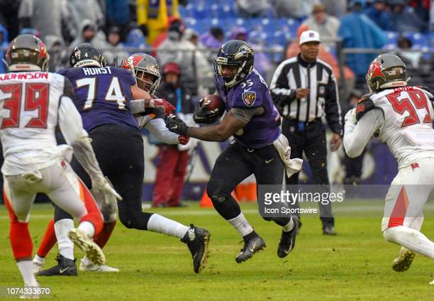 Baltimore Ravens running back Gus Edwards runs with the ball in the second half against Tampa Bay Buccaneers free safety Isaiah Johnson and...