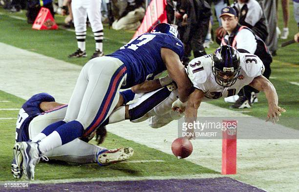 Baltimore Ravens' running back Jamal Lewis stretches the ball over the goal line for a touchdown as two New York Giant defenders attempt to stop him...