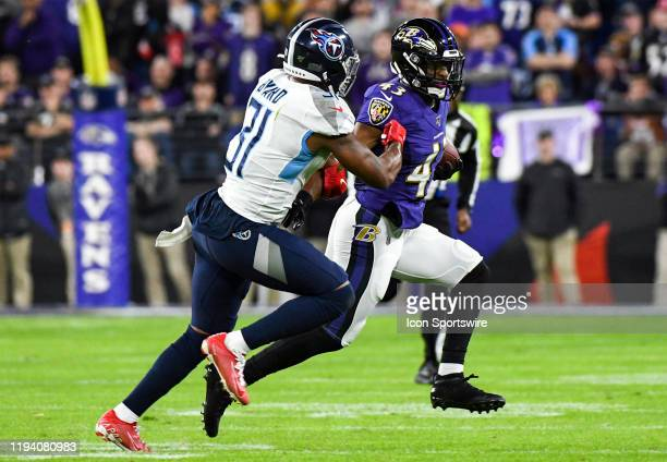 Baltimore Ravens running back Justice Hill retrurns a kickoff against Tennessee Titans tight end Jonnu Smith on January 11 at MT Bank Stadium in...