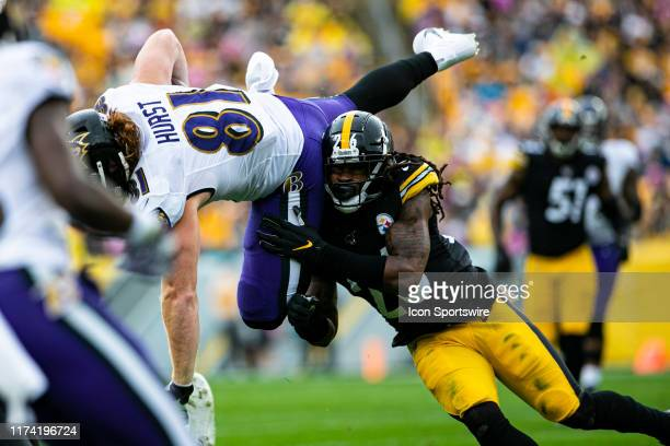 Baltimore Ravens tight end Hayden Hurst is tackled in midair by Pittsburgh Steelers inside linebacker Mark Barron during the NFL football game...