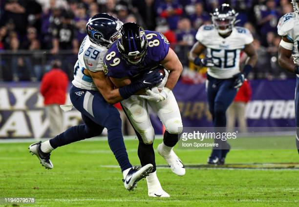 Baltimore Ravens tight end Mark Andrews is brought down by Tennessee Titans inside linebacker Wesley Woodyard on January 11 at MT Bank Stadium in...