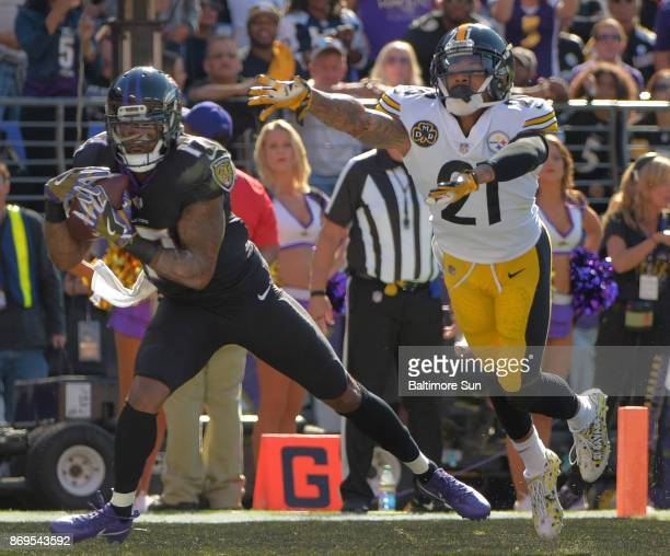 Baltimore Ravens wide receiver Mike Wallace hauls in a Joe Flacco pass in front of Pittsburgh Steelers cornerback Joe Haden to score a touchdown...