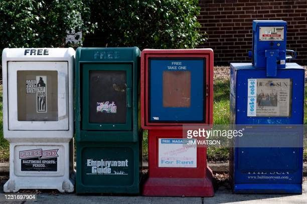 Baltimore Sun newspaper bin stands with others in Baltimore, Maryland on March 11, 2021. - After years of staff cuts, shrinking budgets and declining...