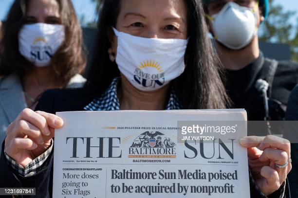 Baltimore Sun reporter Jean Marbella holds up the Baltimore Sun front page that headlined their potential take over by a nonprofit group during an...