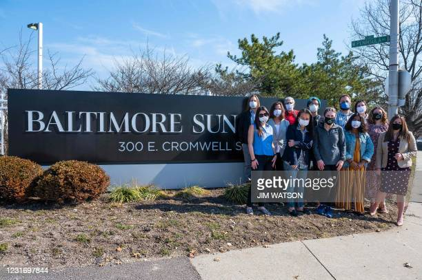 Baltimore Sun reporters gather in front of their sign during an interview in Baltimore, Maryland on March 11, 2021. - After years of staff cuts,...