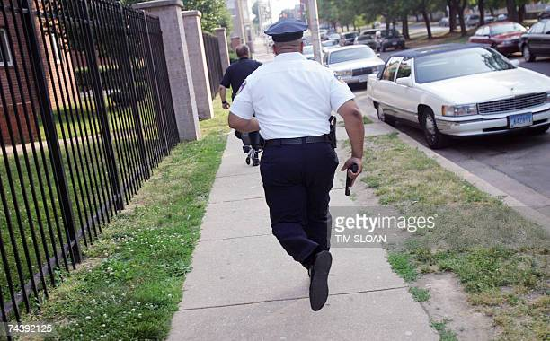 TO GO WITH AFP STORY USCRIMEBALTIMORE Police officers with guns drawn run toward the court yard of the Pedestal Gardens Apartments where a barrage of...