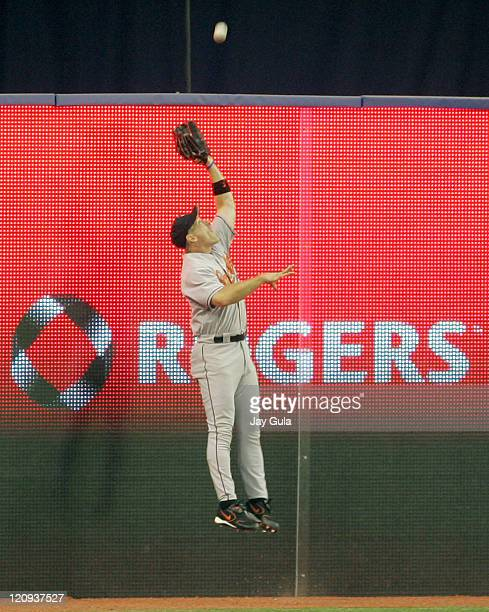Baltimore's BJ Surhoff jumps up against the fence to rob Eric Hinske of a hit in MLB action at Rogers Centre in Toronto Canada on August 30 2005