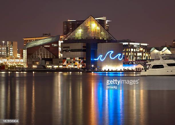 baltimore's inner harbor and national aquarium lit at night - baltimore stock photos and pictures