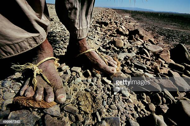 2006 Baluchistan Province Pakistan The feet of an old man shod in the flimsiest of shoes held together only by rope who must walk about thirty...