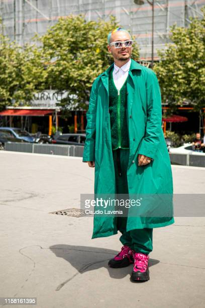 Balvin, wearing a white shirt, green vest, green pants, green long jacket and black and pink shoes, is seen outside Kenzo fashion show on Day 6...