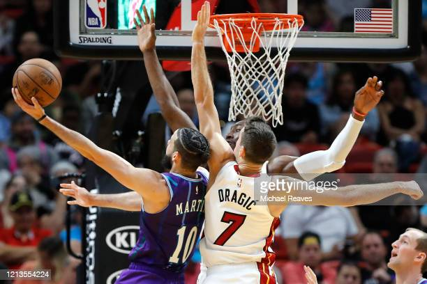 Bam Adebayo and Goran Dragic of the Miami Heat defend a shot by Caleb Martin of the Charlotte Hornets during the second half at American Airlines...