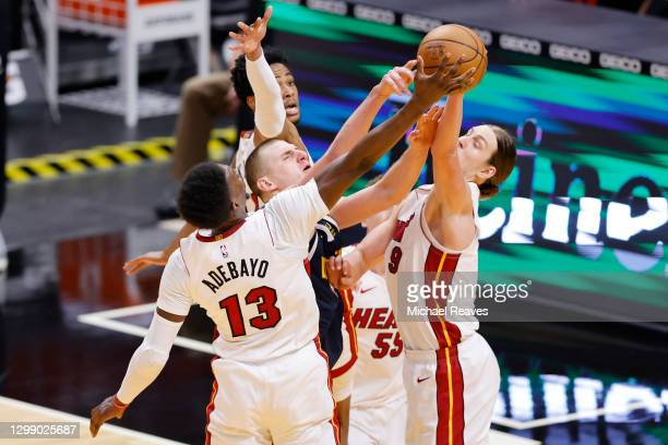 Bam Adebayo and Kelly Olynyk of the Miami Heat defend a shot by Nikola Jokic of the Denver Nuggets during the third quarter at American Airlines...