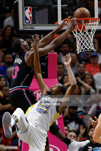Bam Adebayo of the Miami Heat dunks over Kevin Durant of the Golden State Warriors during the first half at American Airlines Arena on February 27...