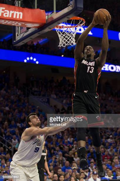 Bam Adebayo of the Miami Heat dunks the ball past Dario Saric of the Philadelphia 76ers during Game One of the first round of the 2018 NBA Playoff at...