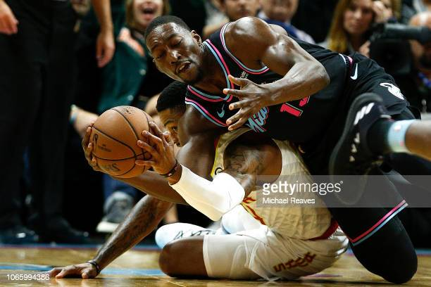Bam Adebayo of the Miami Heat fights for a loose ball with Kent Bazemore of the Atlanta Hawks during the second half at American Airlines Arena on...