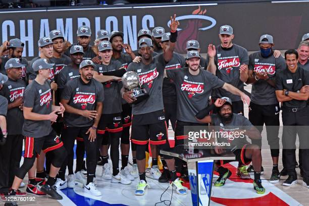 Bam Adebayo of the Miami Heat holds up the Eastern Conference Championship Trophy and poses for a photos with his team after winning Game Six of the...