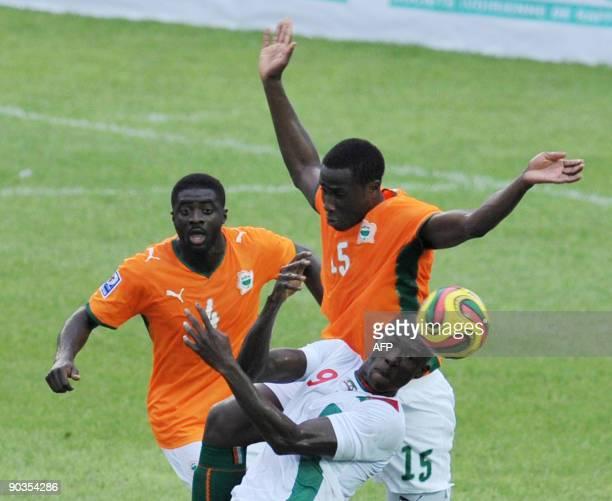 Bamba Souleyman and Kalou Toure Kolo Abib of 'The Elephants' the Ivory Coast's national football team vie with Dagano Moumini of Burkina Faso on...
