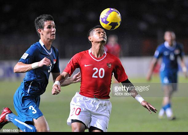 Bambang Pamungkas of Indonesia heads the ball as Singapore's Baihaki moves in during the AFF Suzuki 2008 Cup against Singapore in Jakarta on December...