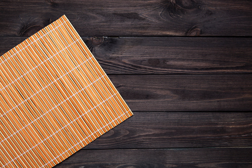 Bamboo mat on wooden table, top view 592361104