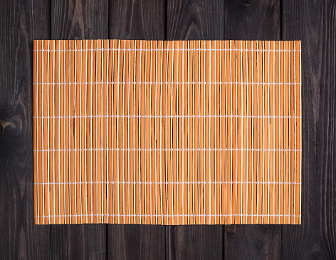 Bamboo mat on wooden table, top view 598704540