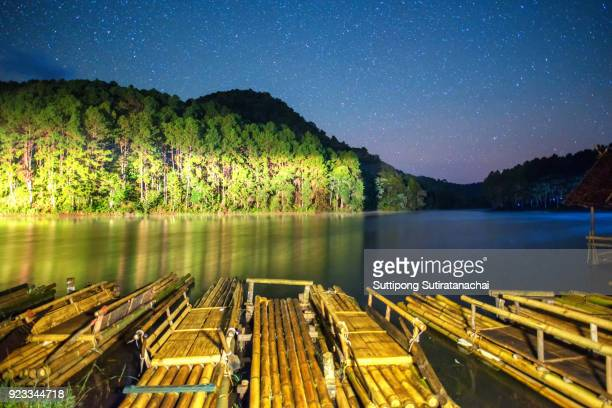 bamboo rafting in lake with landscape of mountain and star