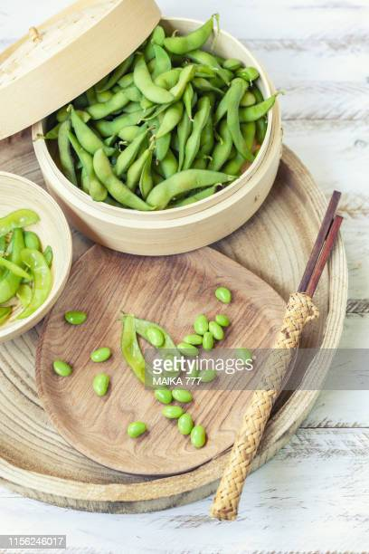 bamboo steamer with boiled edamame and chopsticks - edamame stock pictures, royalty-free photos & images