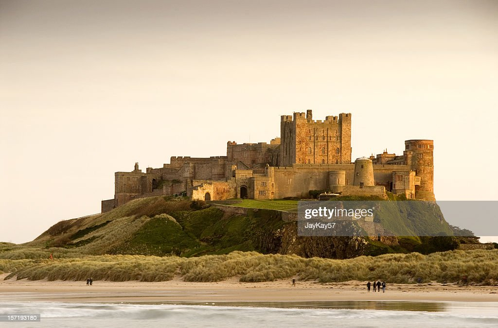 Bamburgh Castle daytime with people walking on beach : Stock Photo