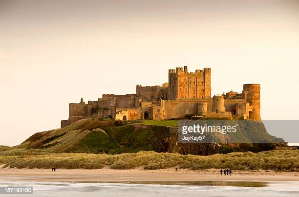 bamburgh castle daytime with people walking on beach - castle stock pictures, royalty-free photos & images