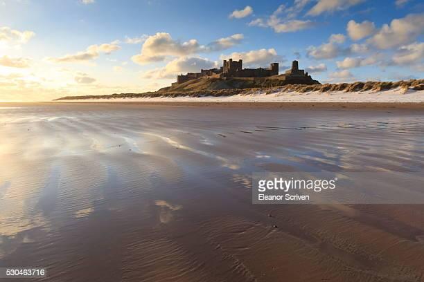 Bamburgh Castle with snow on Bamburgh Beach, Bamburgh, Northumberland, England, United Kingdom, Europe