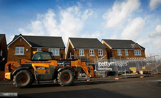 Bamford Excavators Ltd loader moves past houses under construction at Gin Pit Village a residential housing development by Ben Bailey Homes Ltd in...
