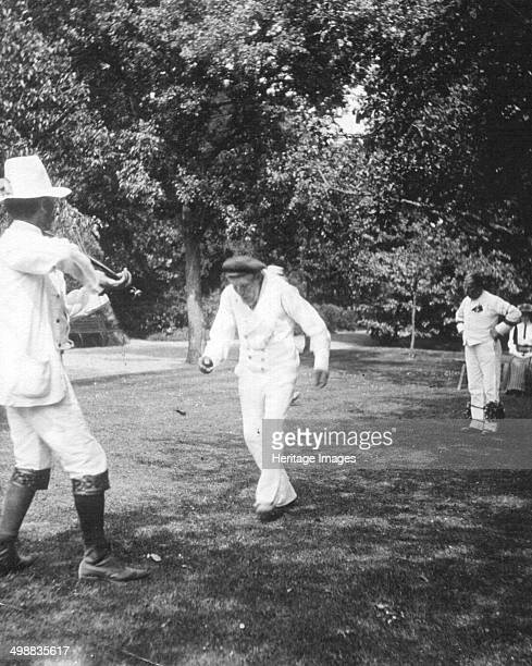 Bampton Morris Dancers, Oxfordshire, Whit Monday, 5 June 1911. William Nathan Wells playing the fiddle, Charles Tanner dancing. Photograph taken...