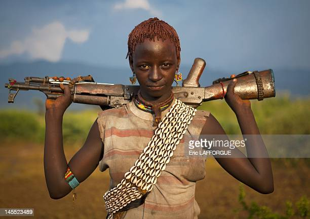 Bana young woman carrying kalashnikov rifle on her shoulders jumping ceremony on June 24 2011 in Omo Valley Ethiopia