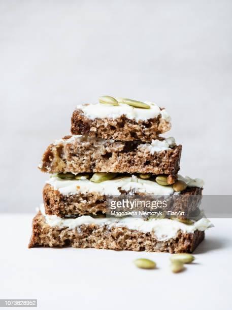 banana bread slices with cream cheese frosting - banana loaf stockfoto's en -beelden