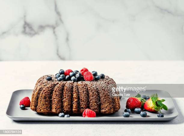 banana bread with berries on a tray on white background - banana loaf stockfoto's en -beelden