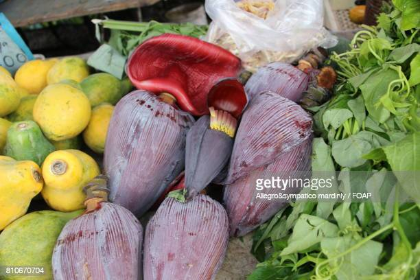 Banana flowers and fruit on market stall