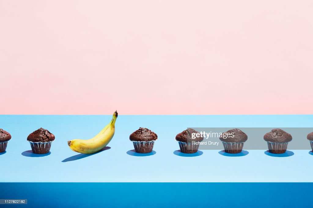 A banana in a row of chocolate cupcakes : Stock Photo