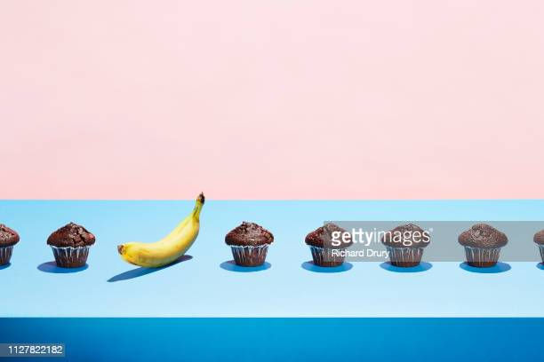 a banana in a row of chocolate cupcakes - individualidad fotografías e imágenes de stock