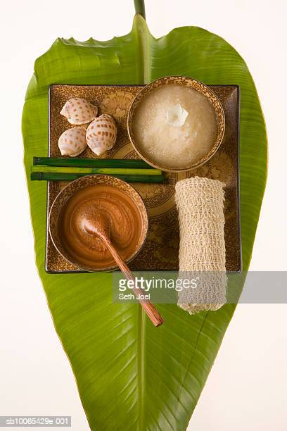 Banana leaf with ceramic bowls containing cosmetic items