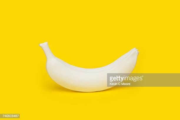 Banana painted white on yellow background