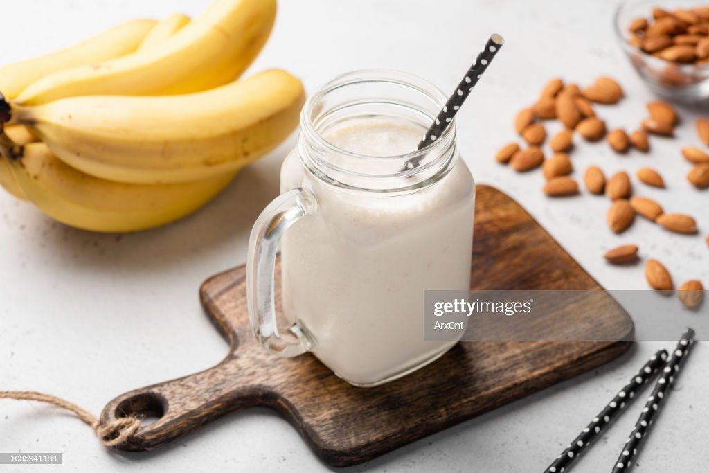 Banana protein smoothie in drinking glass : Stock Photo