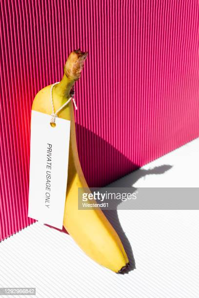 banana with tag private usage only against pink background - vertical stock pictures, royalty-free photos & images