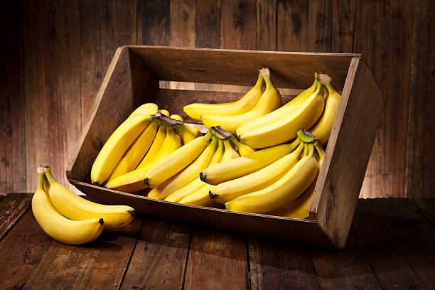 bananas in a crate on rustic wood table - banana stock pictures, royalty-free photos & images